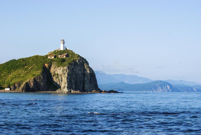E E 在小山顶部的灯塔鲁德内在日本海的岸附近 免版税库存照片