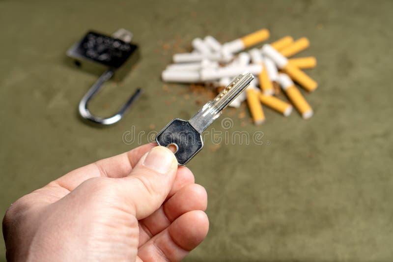 E 在残破的香烟和一个明锁背景的钥匙  免版税库存照片