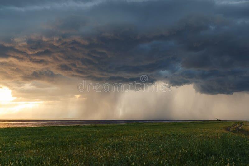 E 在湖的暴风云日落的 绿色领域和草甸 r 库存照片