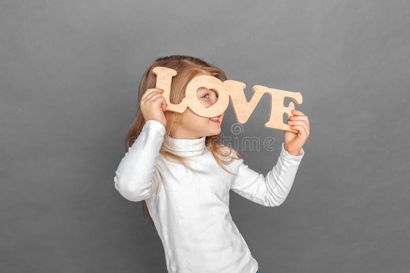 E 在灰色看隔绝的女孩身分通过爱标志微笑嬉戏 免版税库存照片