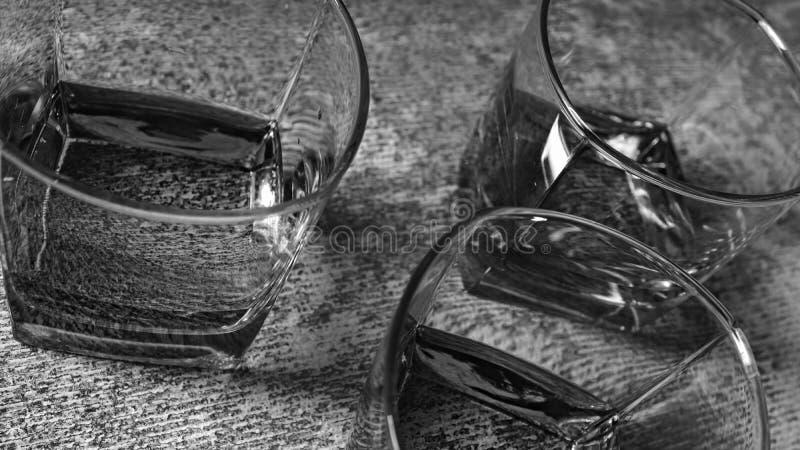 E 在玻璃的威士忌酒在灰色石背景 免版税图库摄影