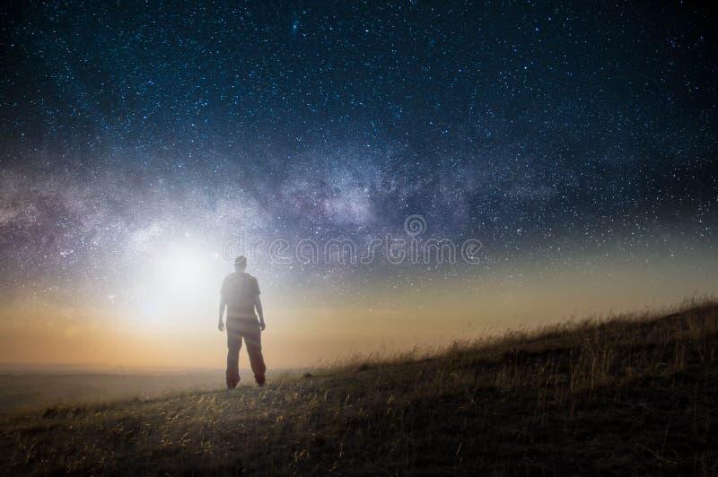 E 在看横跨与明亮的光的空间的小山的一个人身分在天空 免版税库存照片