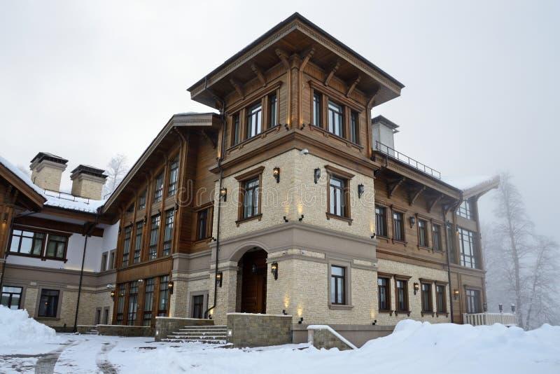 E 在罗莎Khutor滑雪场的瑞士山中的牧人小屋村庄在有雾的1月天 免版税库存照片