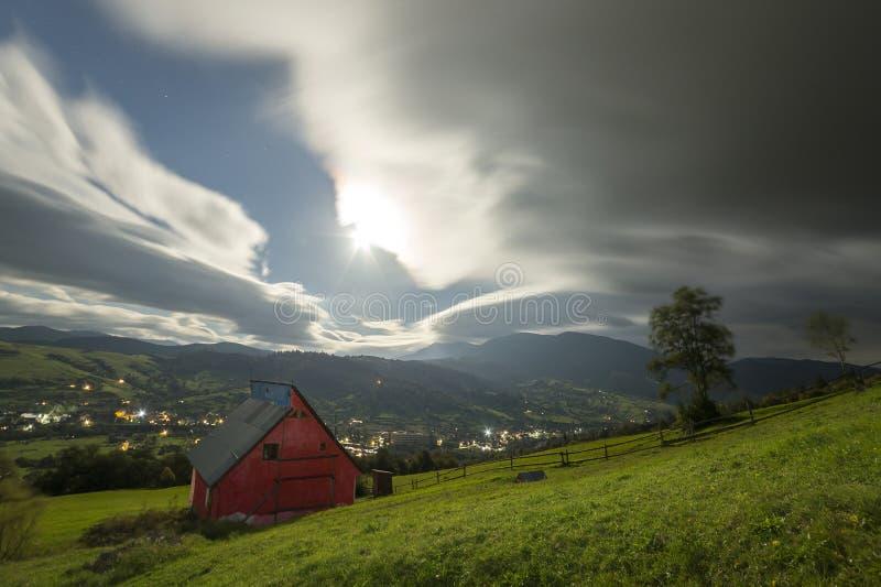 E 在陡峭的山坡的小屋村庄在剧烈的平衡的天空背景,明亮的路与 免版税图库摄影