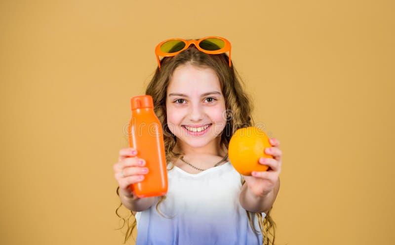 E 夏天维生素饮食 自然维生素来源 愉快的女孩饮料新鲜的橙汁过去 女孩以时尚 库存图片