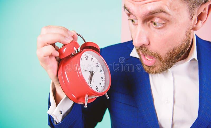 E 多少时刻离开直到最后期限 r 人有胡子的惊奇的商人举行时钟 免版税库存图片