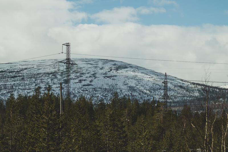 E 多雪的小山和森林输电线在山 库存图片