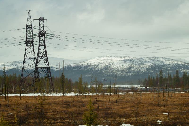 E 多雪的小山和森林输电线在山 库存照片