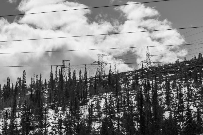 E 多雪的小山和森林输电线在山 图库摄影