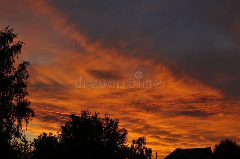 E 天空在日落,黎明 色的云彩,红色,桔子,淡色 在黄昏的浪漫淡色天空 库存图片