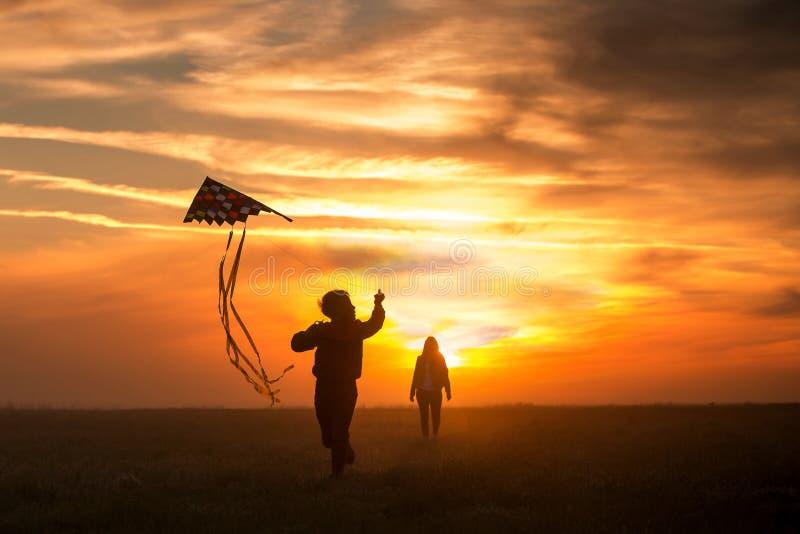 E 女孩和男孩飞行在不尽的领域的一只风筝 明亮的日落 人剪影反对天空的 库存照片