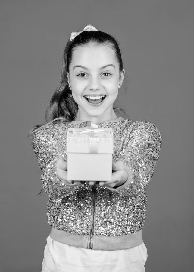 E 女孩有礼物盒蓝色背景 r o 逗人喜爱的可爱的孩子运载礼物盒 图库摄影
