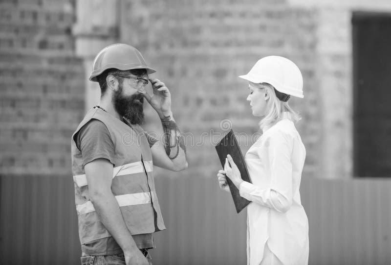 E 妇女工程师和有胡子的残酷建造者谈论建筑进展 ?? 库存照片