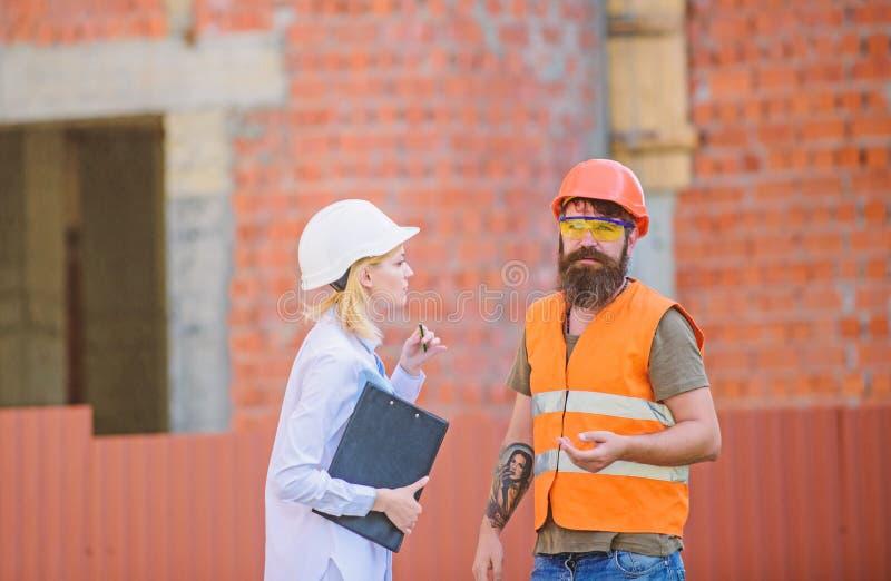 E 妇女工程师和有胡子的残酷建造者谈论建筑进展 工程项目 免版税库存照片