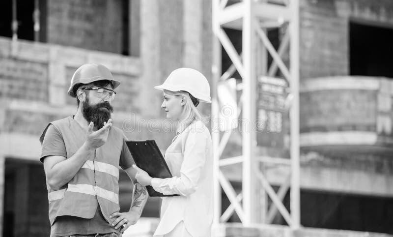 E E 妇女工程师和有胡子的残酷建造者谈论建筑 免版税库存照片