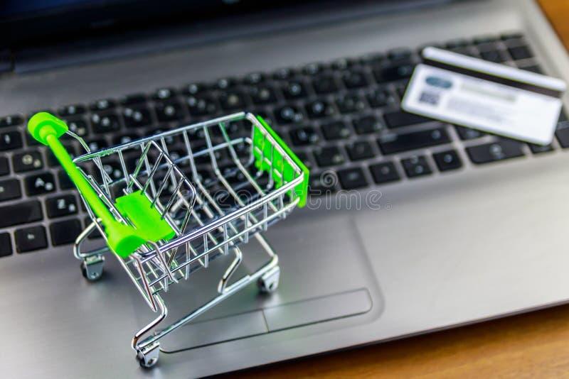 E 小手推车和信用卡在膝上型计算机键盘 免版税库存照片
