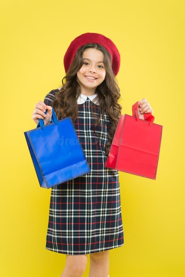E 帽子的女孩 ?? 有购物带来的孩子 黄色的巴黎人孩子 一点秀丽 免版税库存照片