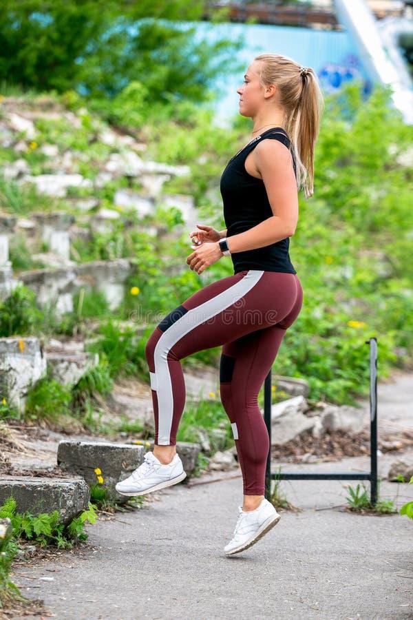 E 年轻女人做与改变的腿的跃迁 r r 免版税库存照片