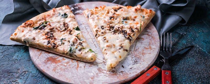 E 意大利hizza用蘑菇和乳酪在一个圆的委员会 叉子、刀子和餐巾 比萨时间概念 库存图片