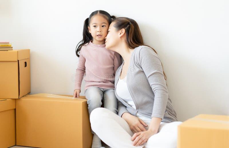 E 打开纸板箱,使用,亲吻和拥抱为他们新的家的母亲和儿童女孩 ?? 免版税库存图片