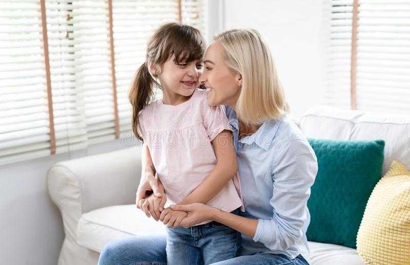 E 拥抱与她的小女儿的母亲是拥抱和微笑在客厅 人们和家庭和 免版税库存照片