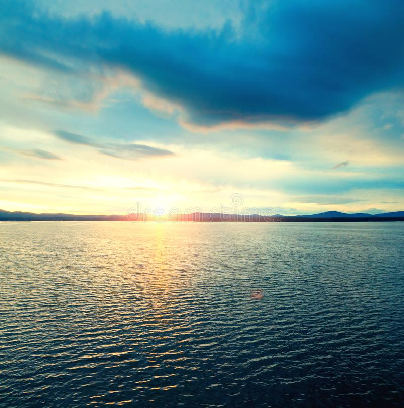 E 日落光点燃的海水表面 r 免版税库存照片