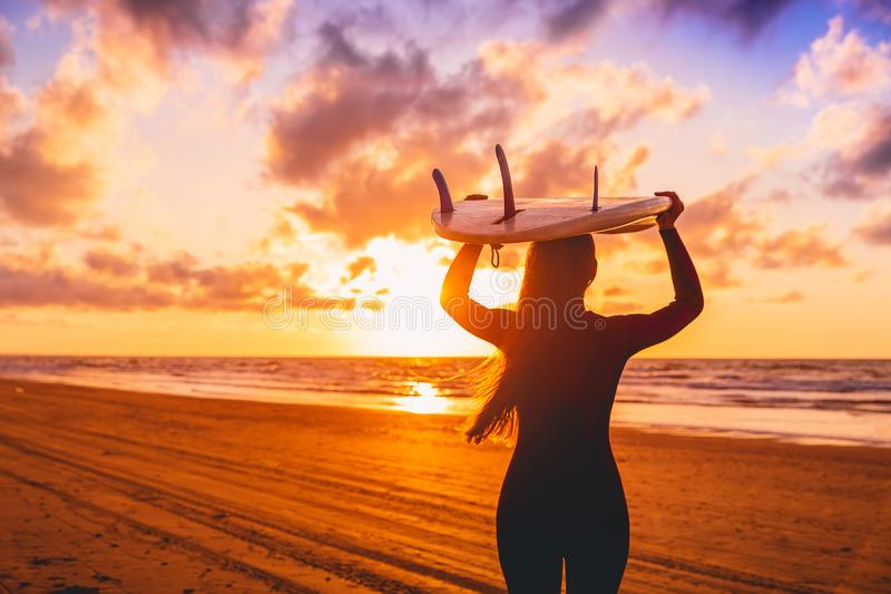 E 有冲浪板的妇女在日落的一个海滩 图库摄影