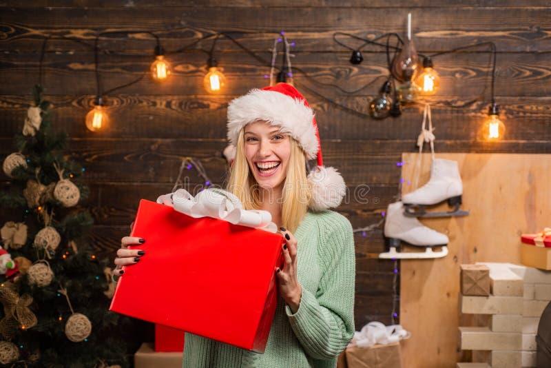 E 有圣诞礼物箱子的年轻女人在圣诞树前面 家庭假日 库存照片