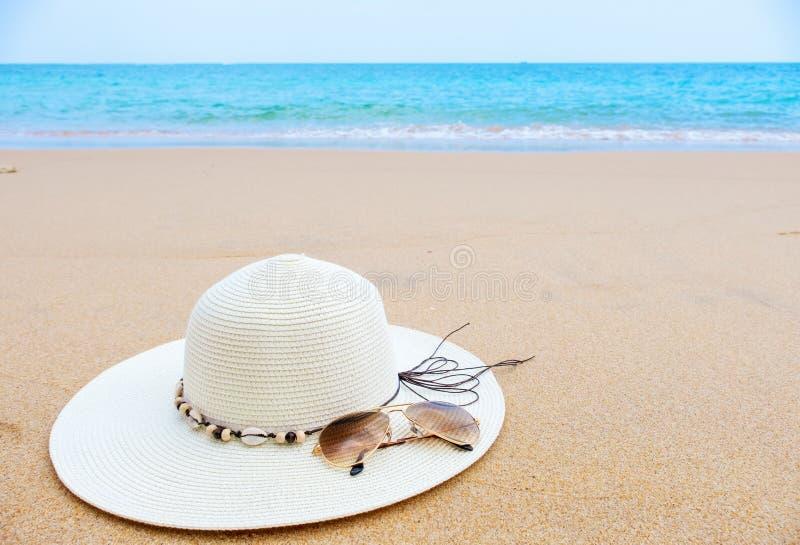 E 有太阳镜的草帽在热带海滩 库存图片