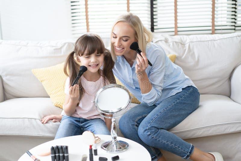 E 有她的小逗人喜爱的女儿的美丽的妈妈做着您的构成并且获得乐趣 妈妈和女儿藏品 库存照片