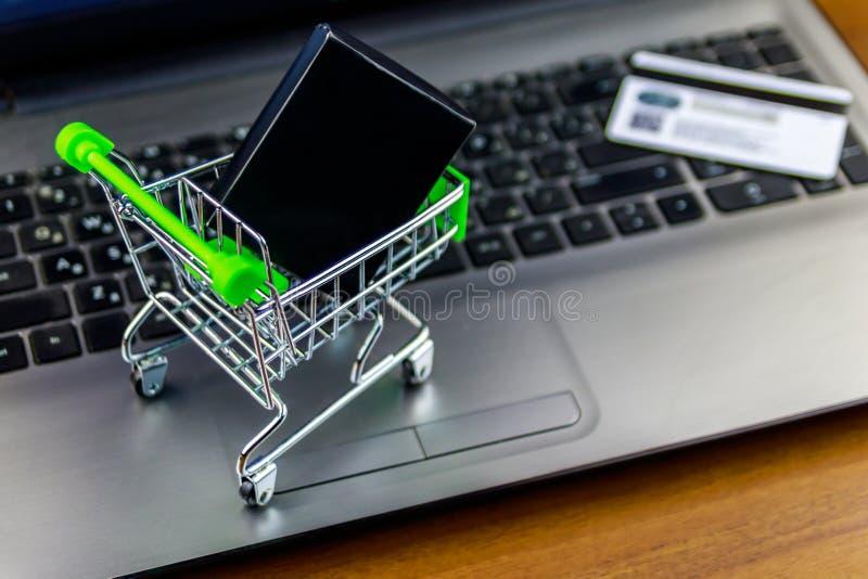 E 有箱子的小手推车和在膝上型计算机键盘的信用卡 库存图片