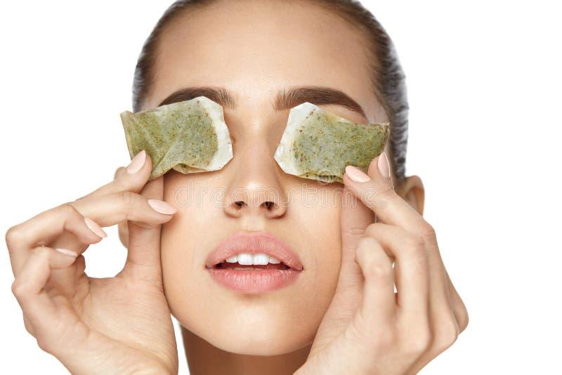 E 有绿茶袋子的美丽的妇女在眼睛下 图库摄影