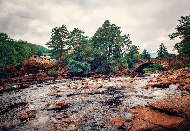 E 有老石桥梁和房子的在背景中,苏格兰高地山河 库存图片
