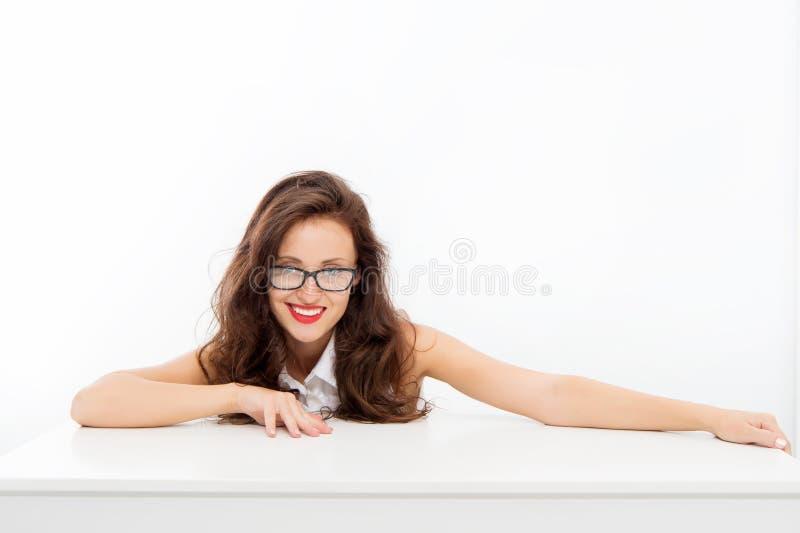 E 有长的卷发的微笑的妇女 在白色隔绝的聪明的老师 学生在桌上 r 库存照片
