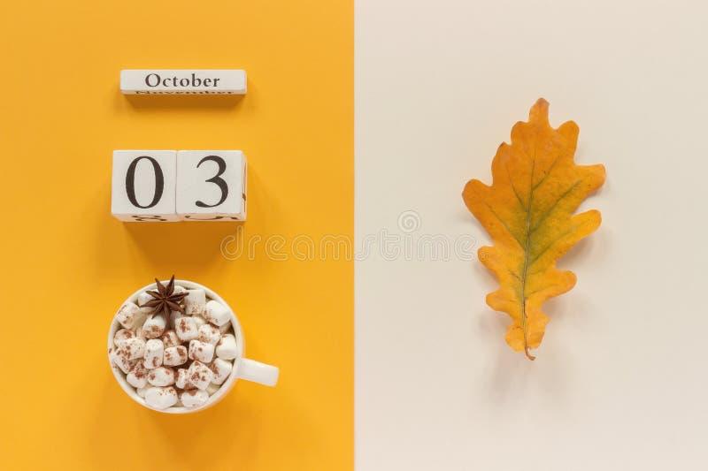 E 木日历10月3日,杯子可可粉用蛋白软糖和在黄色米黄背景的黄色秋叶 免版税库存图片