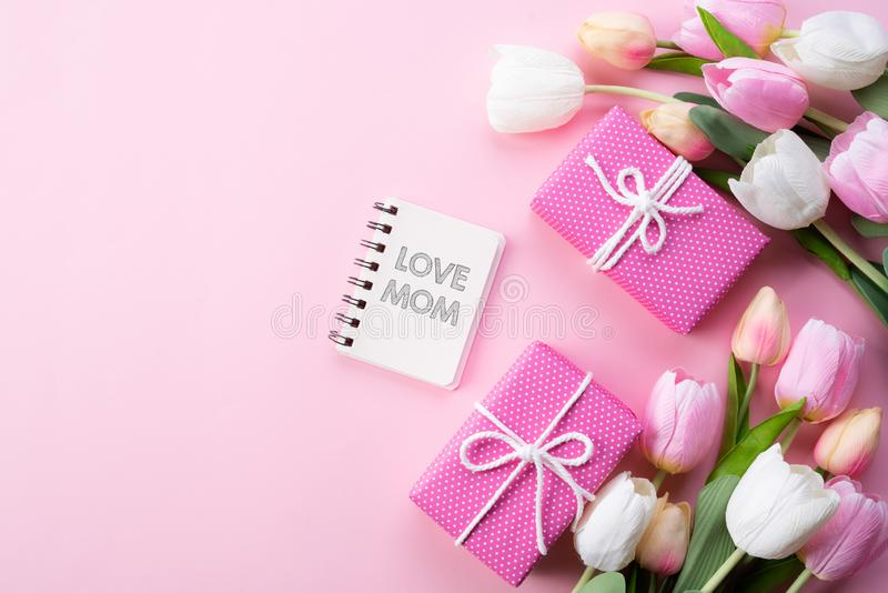 E 桃红色郁金香花、礼物盒和笔记本顶视图与爱妈妈文本在桃红色淡色背景 库存图片