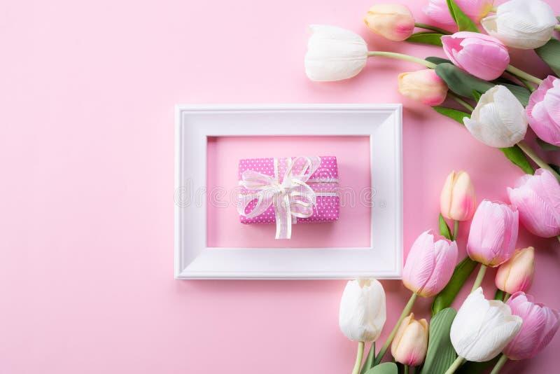 E 桃红色郁金香花和白色相框顶视图有礼物盒的在桃红色淡色背景 ?? 免版税库存照片