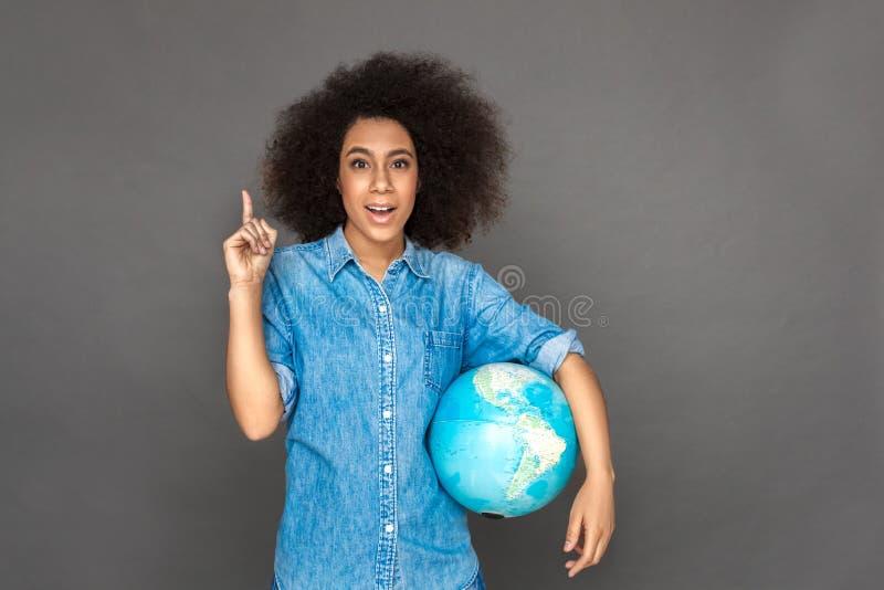 E 混血儿在灰色隔绝的妇女身分与指向微笑的地球地球激动 免版税库存图片