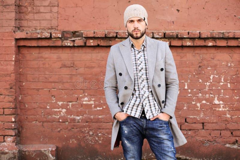 E 灰色外套和帽子身分的时髦的年轻人在街道上在城市 库存图片
