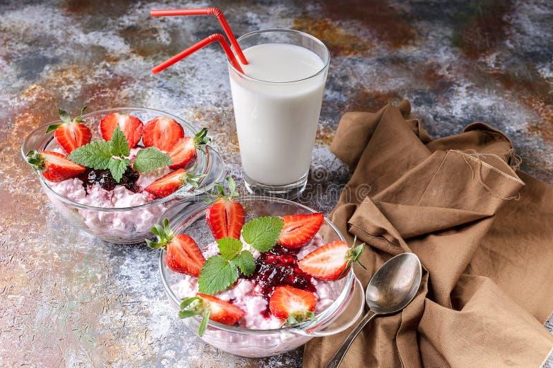 E 牛奶、酸奶干酪、果酱、酸奶用新鲜的草莓和薄荷叶 免版税库存图片