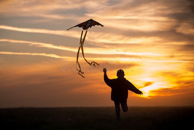 E 男孩横跨与风筝的领域跑 一个孩子的剪影反对天空的 明亮的日落 免版税库存图片