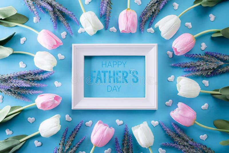 E 白色桃红色郁金香花和相框顶视图有愉快的父亲节文本的在明亮的蓝色 库存照片