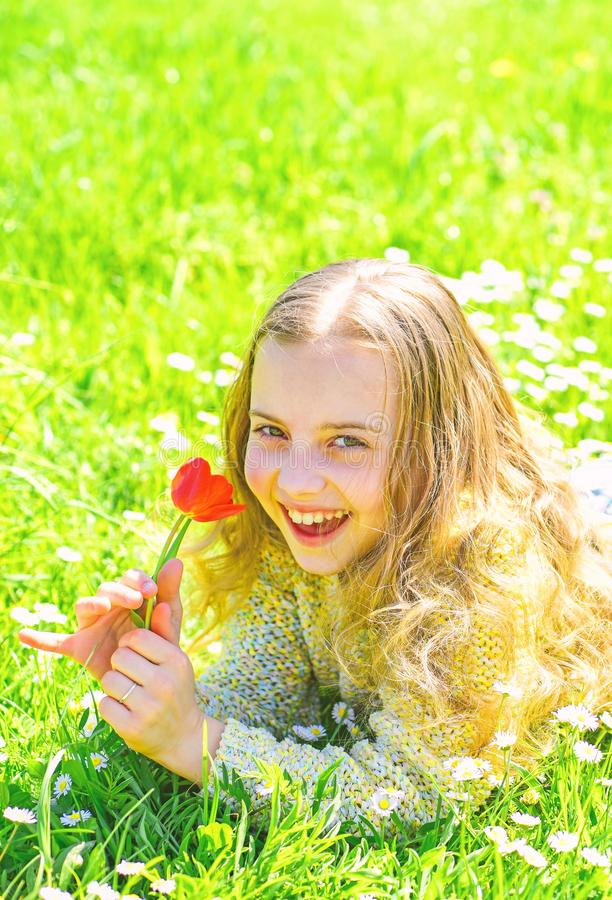 E E 笑容的女孩拿着红色郁金香花,嗅 免版税库存图片