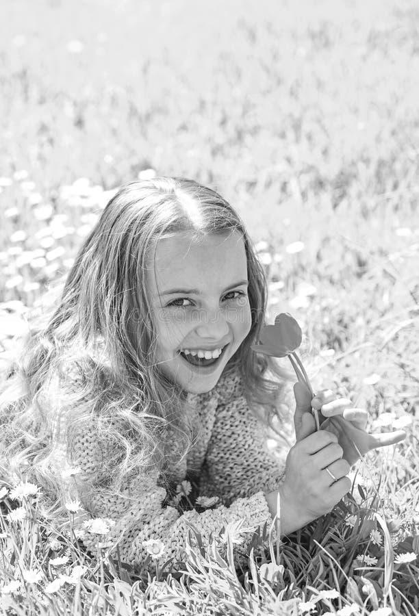E E 笑容的女孩拿着红色郁金香花,嗅 免版税图库摄影