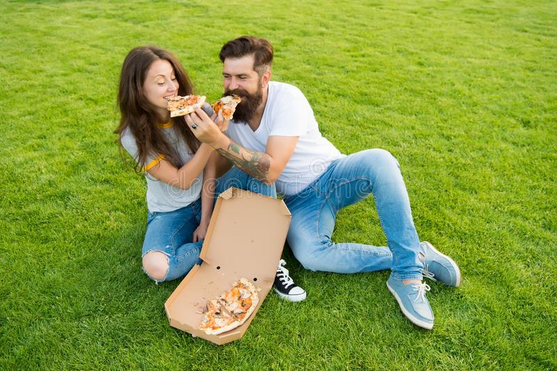 E 结合吃放松在绿色草坪的比萨 r 有胡子的人和女朋友享用低贱 免版税库存图片
