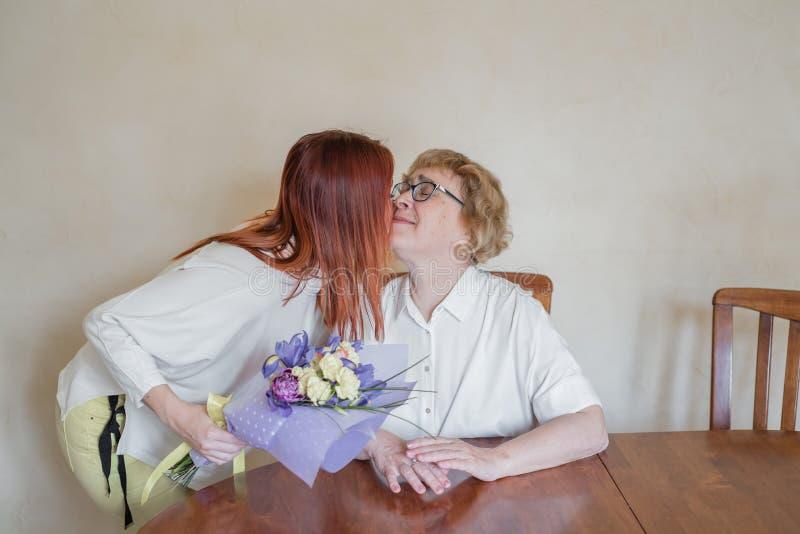 E 给花照顾和亲吻她的女儿在面颊 花费时间一起, 免版税库存图片