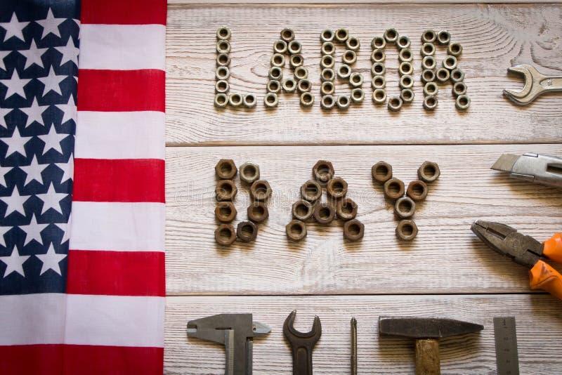 E 美国国旗和题字劳动节和各种各样的工具在轻的木背景 免版税库存照片