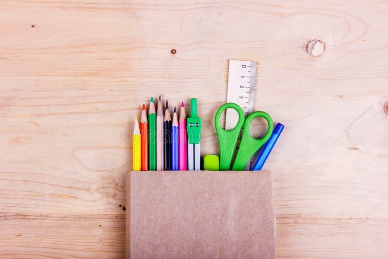 E 色的铅笔,剪刀,统治者,在包装纸袋子的指南针 库存照片