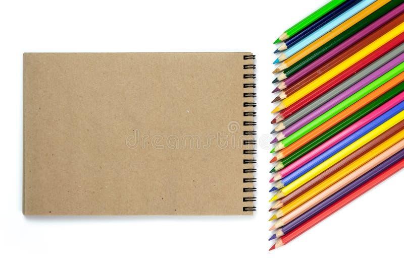 E 色的铅笔,在棕色和米黄背景的笔记本 设计观念-笔记本和颜色铅笔顶视图  免版税库存图片