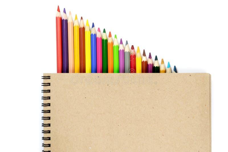 E 色的铅笔,在棕色和米黄背景的笔记本 设计观念-笔记本和颜色铅笔顶视图  库存照片